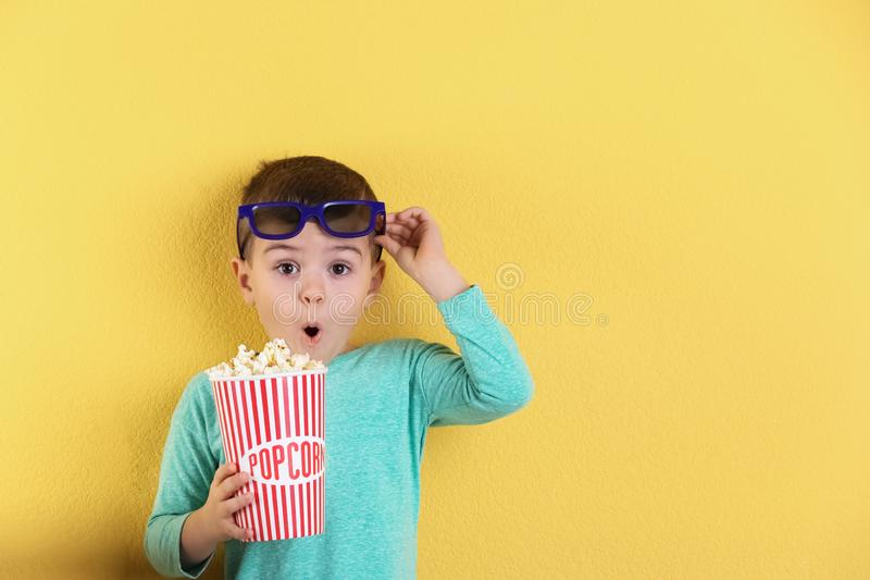 Netter kleiner Junge mit Popcorn und Gläsern auf Farbhintergrund stockbilder