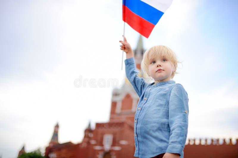 Netter kleiner Junge mit russischer Flagge mit Spasskaya-Turm Russland, Moskau auf Hintergrund lizenzfreie stockbilder