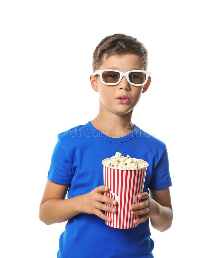 Netter kleiner Junge mit Schale des aufpassenden Films des Popcorns auf weißem Hintergrund stockfotografie