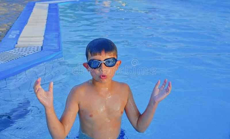Netter kleiner Junge mit Schwimmenschutzbrillen im Swimmingpool am Sommertag Sommer und glückliches Kindheitskonzept Kopieren Sie lizenzfreies stockfoto