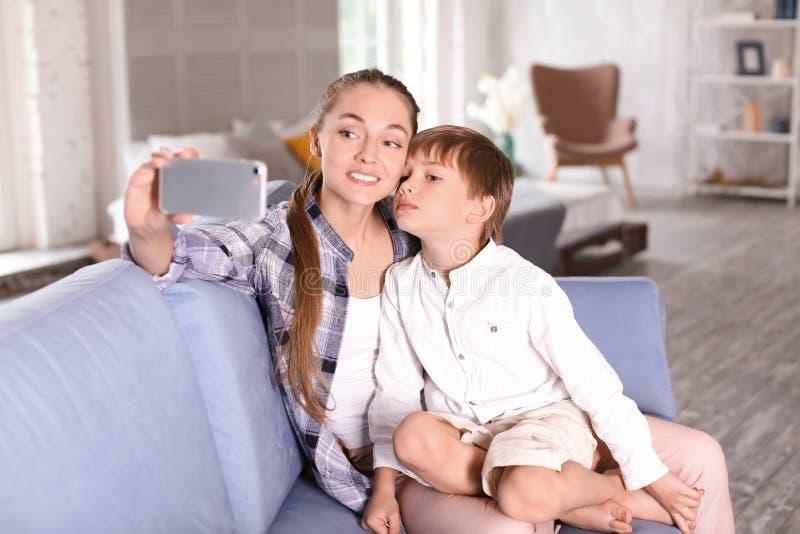 Netter kleiner Junge mit seiner Mutter, die zu Hause selfie nimmt stockfotografie