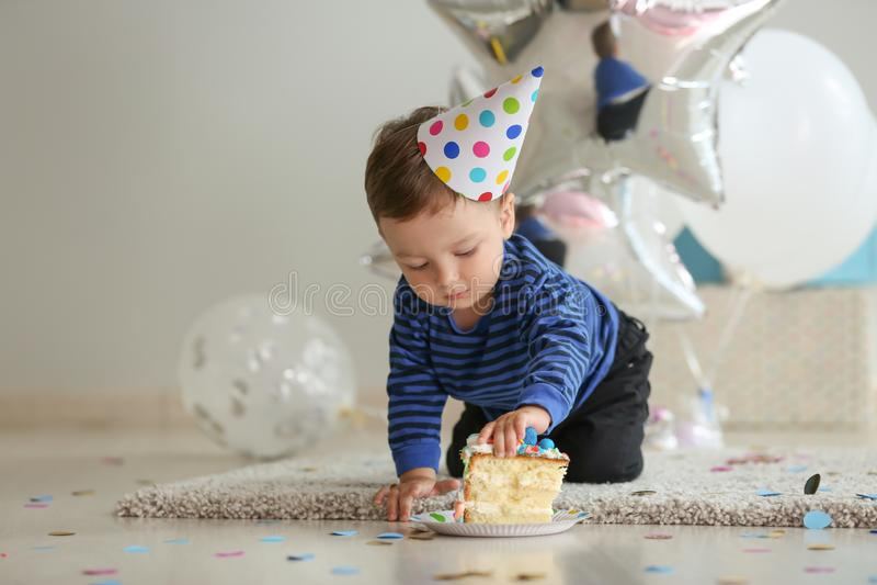 Netter kleiner Junge mit Stück des Geburtstagskuchens im Raum stockfoto