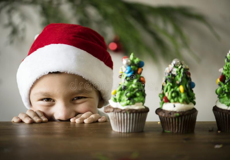 Netter kleiner Junge mit Weihnachtsbaum verzierte kleine Kuchen lizenzfreie stockbilder
