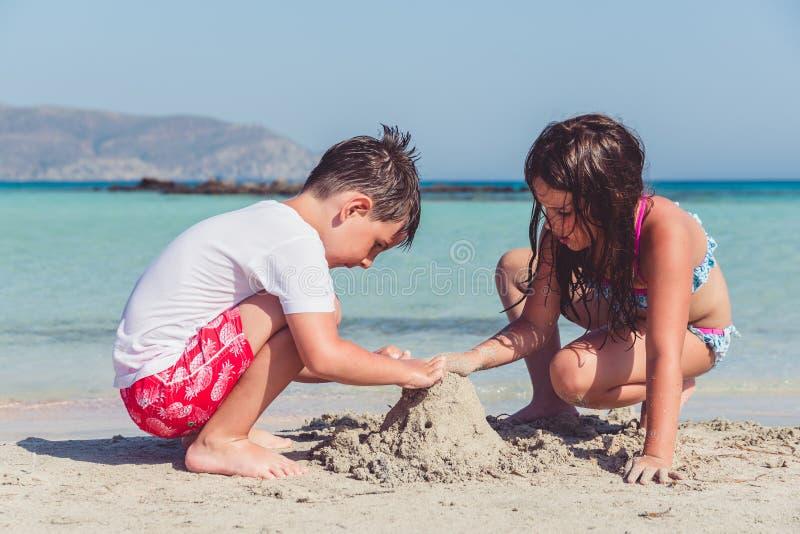 Netter kleiner Junge und ein Mädchen, das ein Sandburg auf einem tropischen Seeufer errichtet stockbild