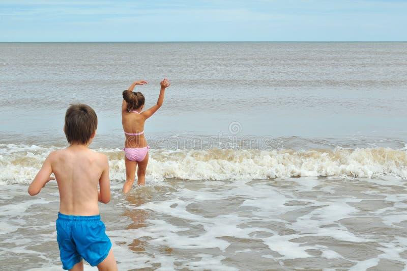 Netter kleiner Junge und Mädchen, spielend in der Welle auf Strand