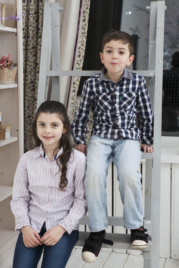 Netter kleiner Junge und Schwester, die auf dem Treppenhaus sitzt lizenzfreie stockbilder
