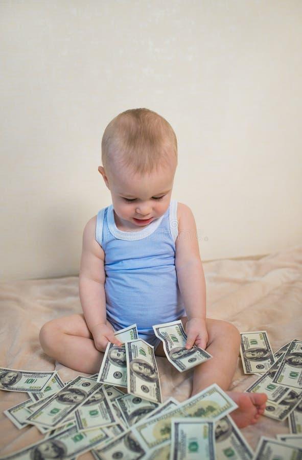 Netter kleiner Junge zählt Geld lizenzfreie stockfotografie