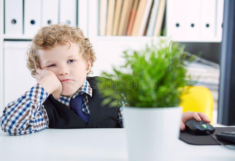 Netter kleiner kaukasischer Junge hält seinen Kopf auf seiner Hand und ahmt müden Büroangestellten oder Wirtschaftler nach Porträ lizenzfreie stockbilder