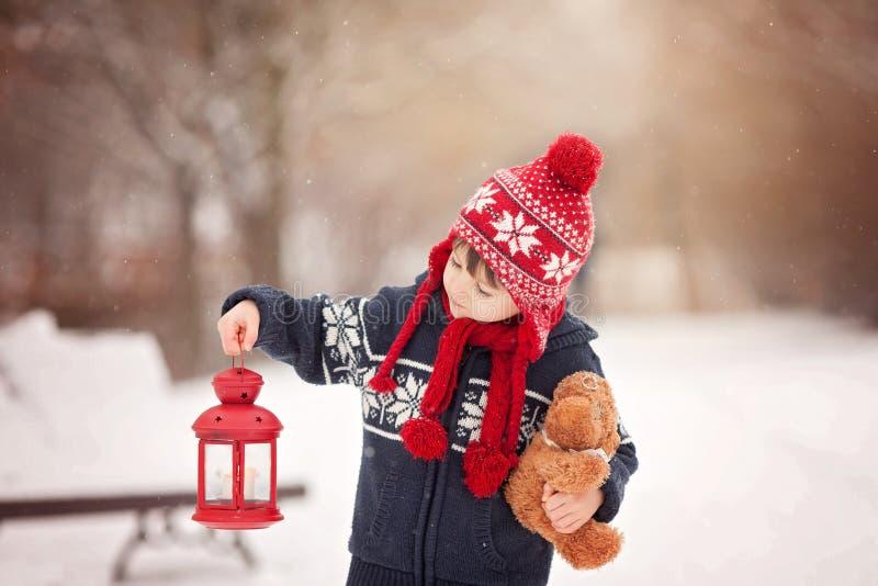 Netter kleiner kaukasischer Junge mit Teddybären und roter Laterne, playi stockfotos
