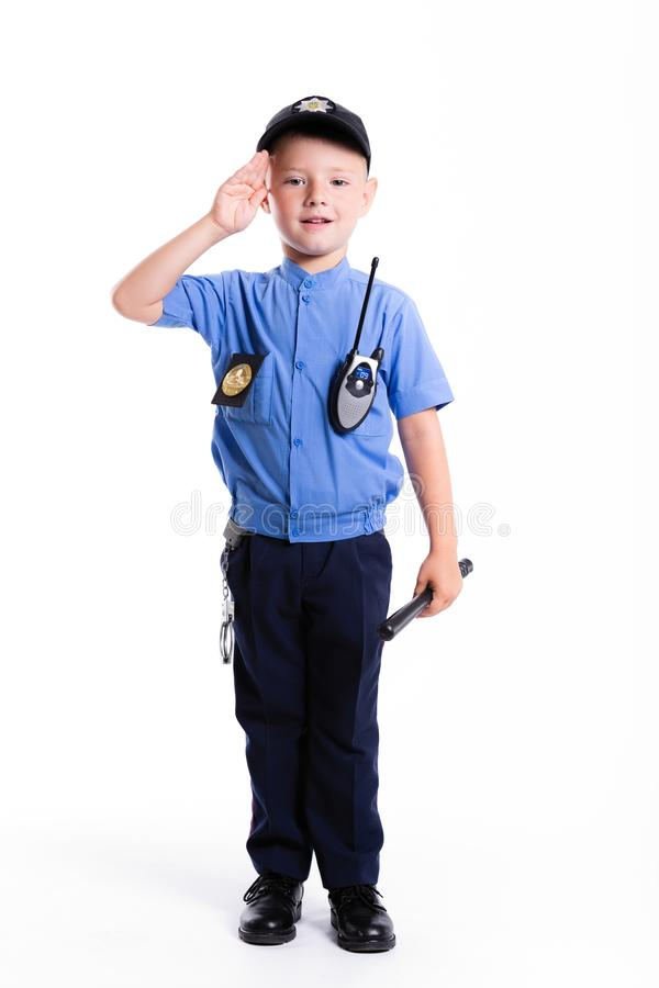 Netter kleiner Polizeijunge mit Lächeln auf Gesicht und Gewehr auf weißem backg stockfotografie