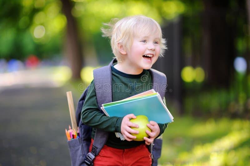 Netter kleiner Schüler mit seinem Rucksack und Apfel Zurück zu Schule-Konzept lizenzfreie stockfotografie