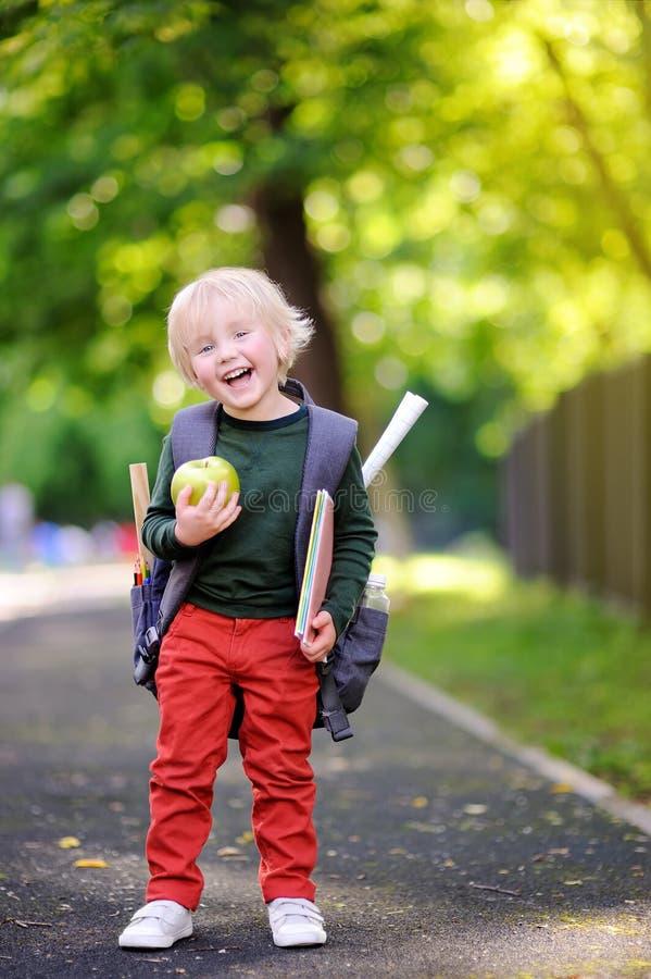 Netter kleiner Schüler mit seinem Rucksack und Apfel Zurück zu Schule-Konzept lizenzfreies stockfoto