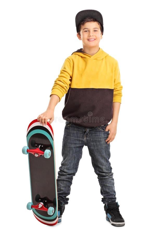 Netter kleiner Schlittschuhläuferjunge, der ein Skateboard hält stockbilder