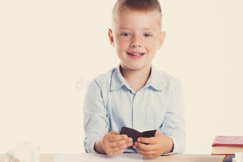 Netter kleiner Schuljunge mit dem enormen Lächeln, das an seinem Schreibtisch auf weißem Hintergrund sitzt Glückliche intelligent lizenzfreie stockfotografie