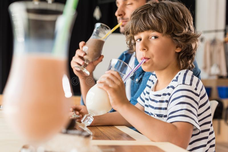 netter kleiner Sohn und seine trinkenden Milchshaken des Vaters lizenzfreies stockbild