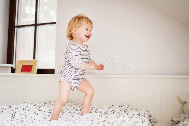 Netter Kleinkindjunge, der auf das Bett springt stockbild