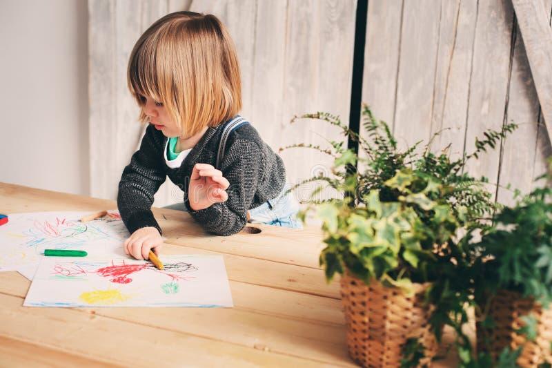 Netter Kleinkindjunge, der zu Hause zeichnet stockbilder