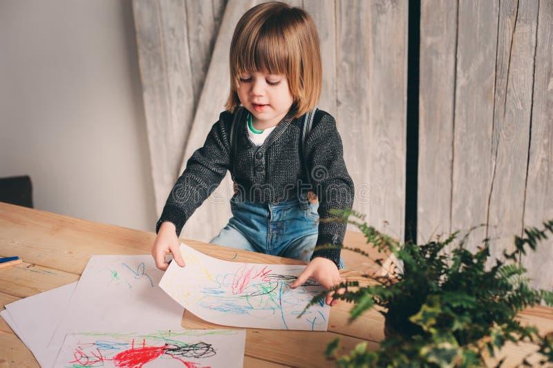 Netter Kleinkindjunge, der zu Hause zeichnet lizenzfreie stockfotografie