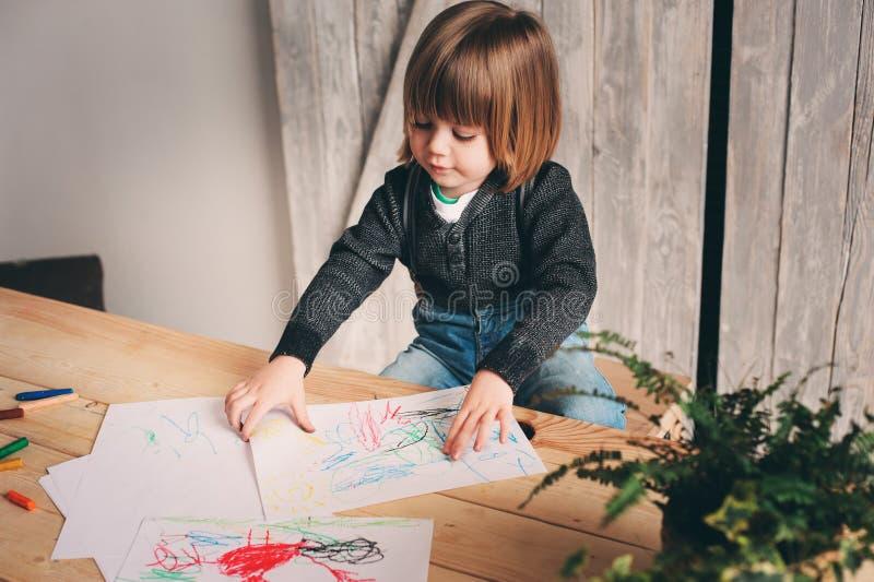 Netter Kleinkindjunge, der zu Hause zeichnet lizenzfreies stockfoto