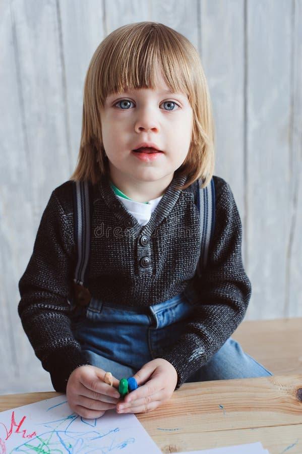 Netter Kleinkindjunge, der zu Hause zeichnet stockfotografie