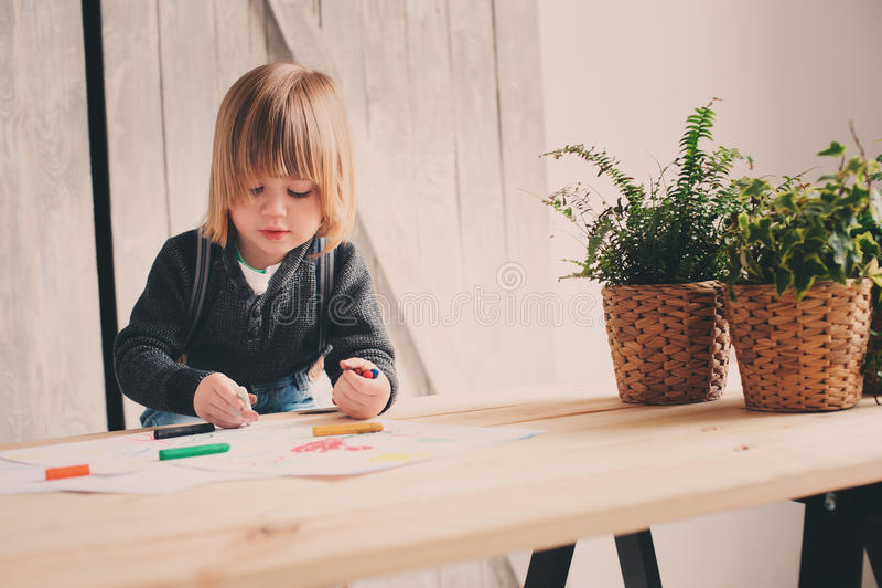 Netter Kleinkindjunge, der zu Hause zeichnet stockfoto