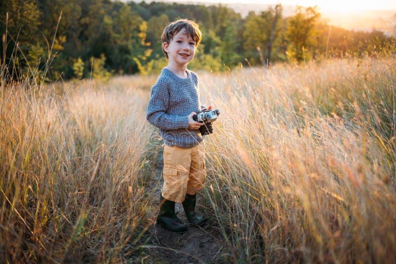 Netter Kleinkindjunge mit alter Retro- Weinlesekamera auf Herbstgrashintergrund Kind mit dem gelockten Haar und dem grauen Mantel lizenzfreies stockbild