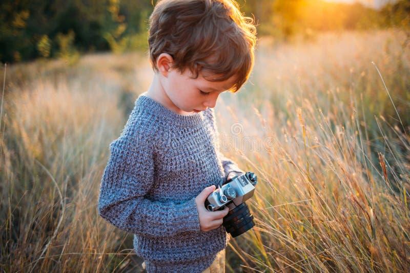 Netter Kleinkindjunge mit alter Retro- Weinlesekamera auf Herbstgrashintergrund Kind mit dem gelockten Haar und dem grauen Mantel stockbild