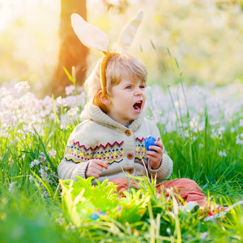 Netter Kleinkindjunge mit den Häschenohren, die Spaß mit traditionellen Ostereiern haben, jagen am warmen sonnigen Tag, draußen stockfotografie