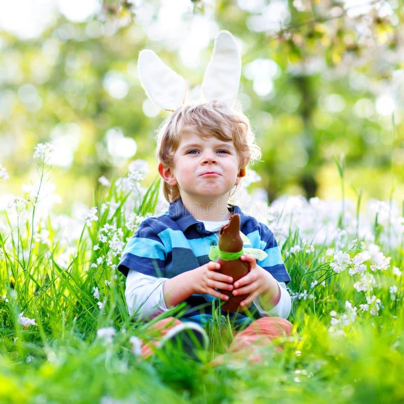 Netter Kleinkindjunge mit den Osterhasenohren Kinderessenschokoladen-Kaninchen fugure des traditionellen Festes an feiernd glückl lizenzfreie stockbilder