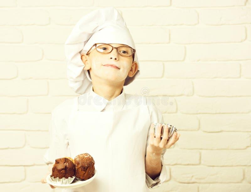 Netter Kochchef des Jungen in der weißen Uniform und im Hut auf beflecktem Gesichtsmehl mit den Gläsern, die Schokoladenkuchen au lizenzfreies stockbild