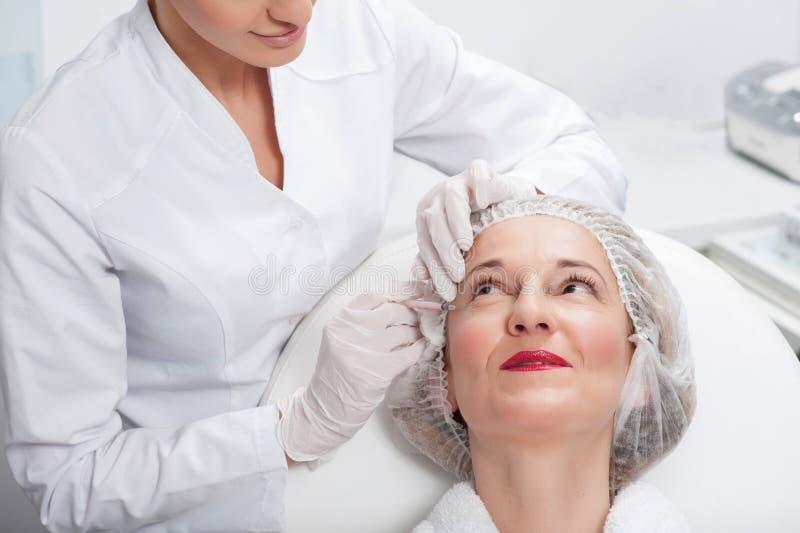 Netter Kosmetiker macht ihren Patienten jünger stockbild