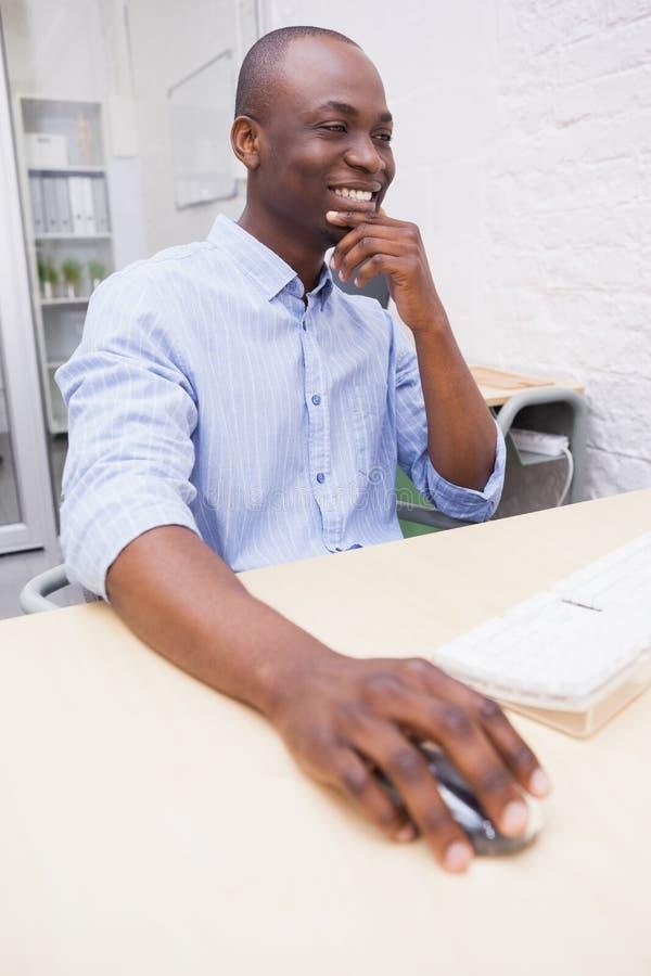 Netter kreativer Geschäftsmann, der an Computer arbeitet lizenzfreie stockbilder
