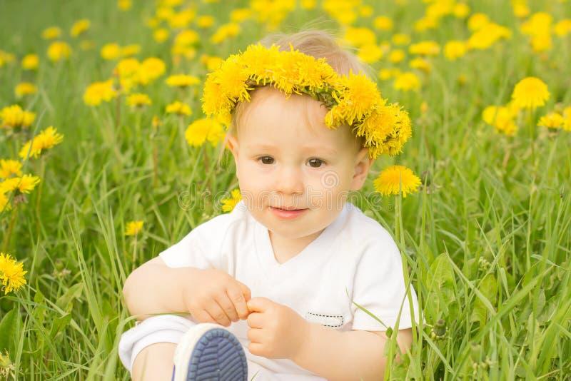 Netter lächelnder Junge auf dem Gebiet des Löwenzahnkranzes im Frühjahr lizenzfreie stockfotografie