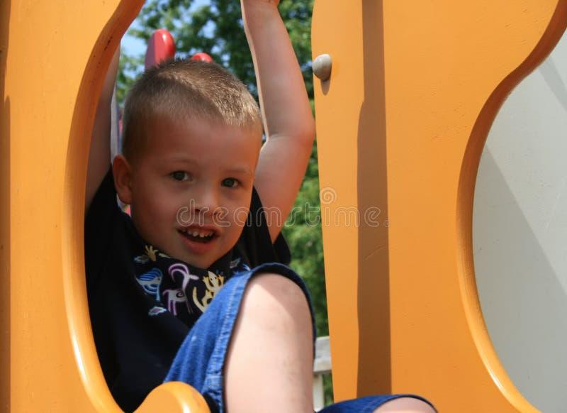 Netter, lächelnder junger Junge auf Spielplatz-Ausrüstung lizenzfreie stockfotos