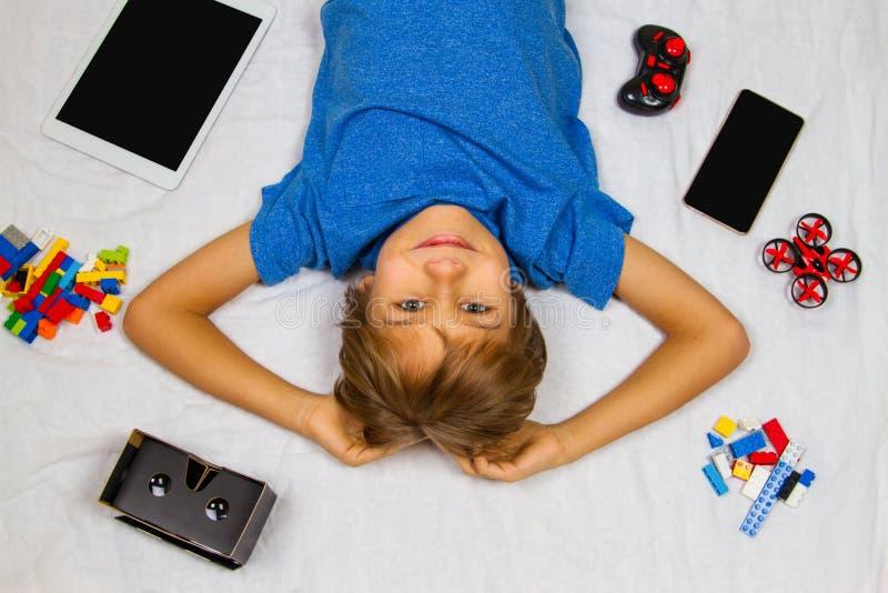 Netter lächelnder kleiner Junge, der im weißen Bett liegt und Kamera betrachtet Handy, Tablet-Computer, Brummen und VR-Gläser lizenzfreie stockfotografie