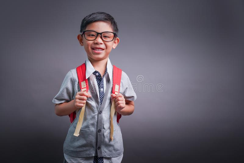 Netter lächelnder kleiner Junge mit großem Rucksack Betrachten der Kamera Auf schwarzem Hintergrund mit copyspace Zur?ck zu Schul lizenzfreies stockbild
