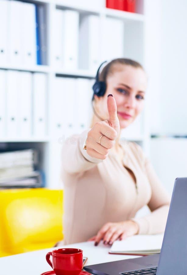 Netter lächelnder weiblicher Kundendienstbetreiber, der Daumen oben im Büro zeigt stockfotos