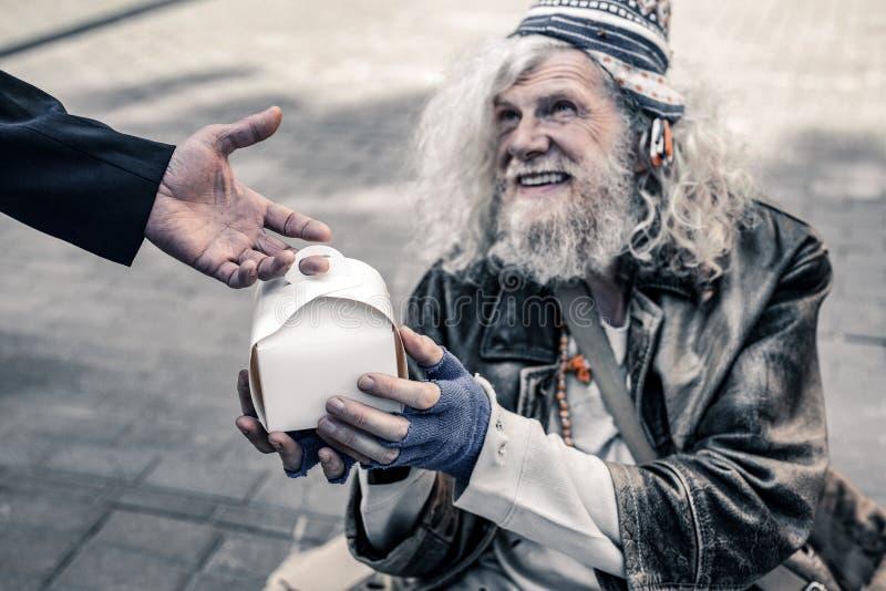 Netter langhaariger alter Mann, der auf der Straße lebt und Kasten mit Nahrung hält lizenzfreie stockbilder
