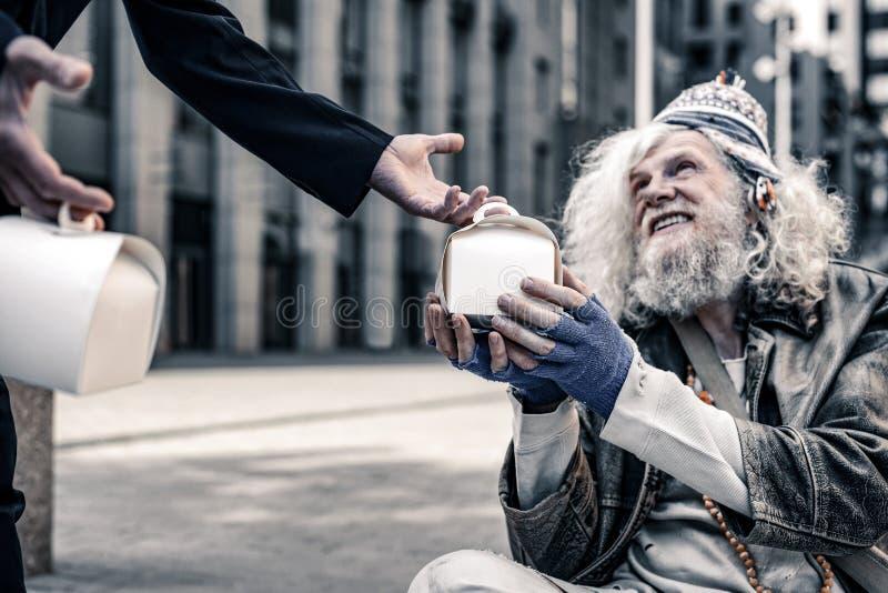 Netter langhaariger armer Mann, der beim Empfangen des Kastens mit Nahrung aufgeregt wird lizenzfreies stockbild