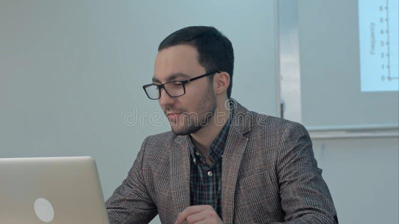 Netter Lehrer, der an Laptop in der Bildungsklasse arbeitet lizenzfreies stockbild