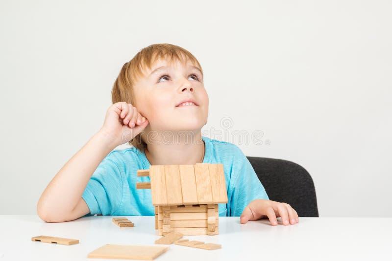 Netter liitle Junge, der ein Haus baut Kind schauen oben und träumend über das Haus, lokalisiert auf Weiß Intelligentes Kind, das stockfoto