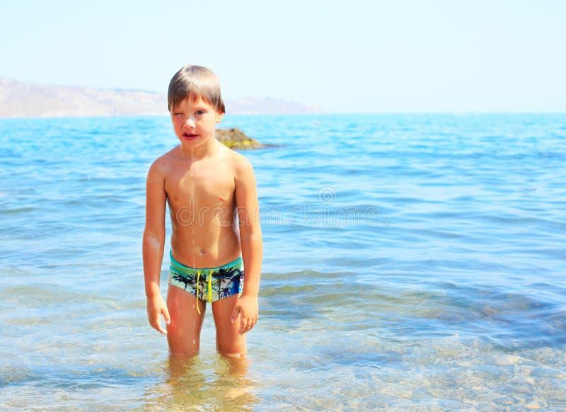 Netter llittle Junge genießen Spiel mit Wasser auf Strand stockbild