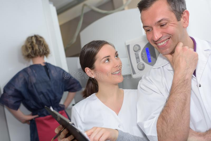 Netter männlicher Doktor und Assistent, die digitale Tablette beim Lachen hält stockfotografie