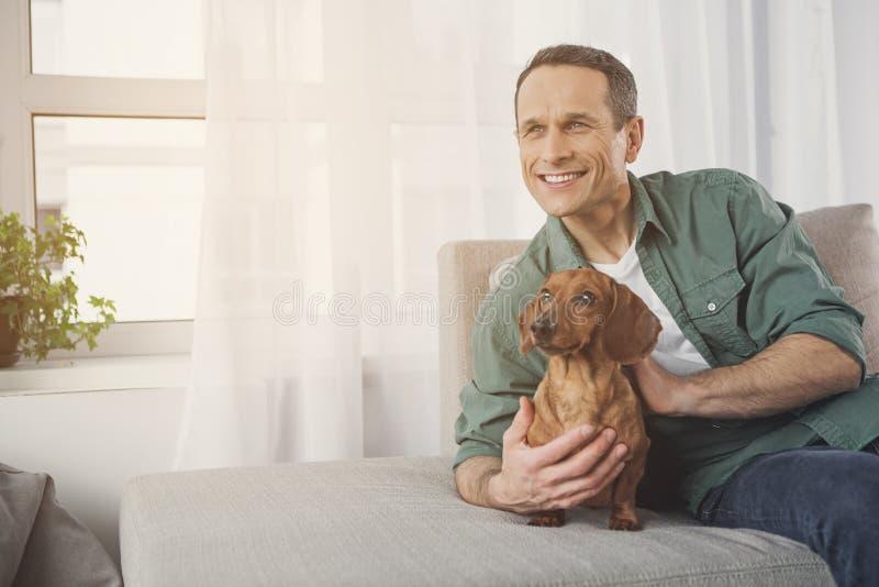 Netter männlicher Inhaber, der auf Sofa mit Haustier sich entspannt stockfotos