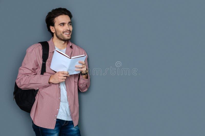 Netter männlicher Tourist, der einen Reiseführer liest lizenzfreie stockfotos