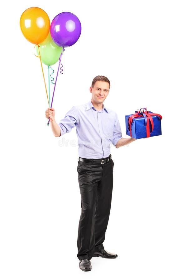 Netter Mann, der Ballone und ein Geschenk hält stockfotos