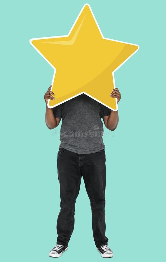 Netter Mann, der ein goldenes Sternbewertungssymbol hält stockfotografie