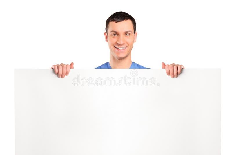 Netter Mann, der hinter einer Leerplatte steht stockbilder