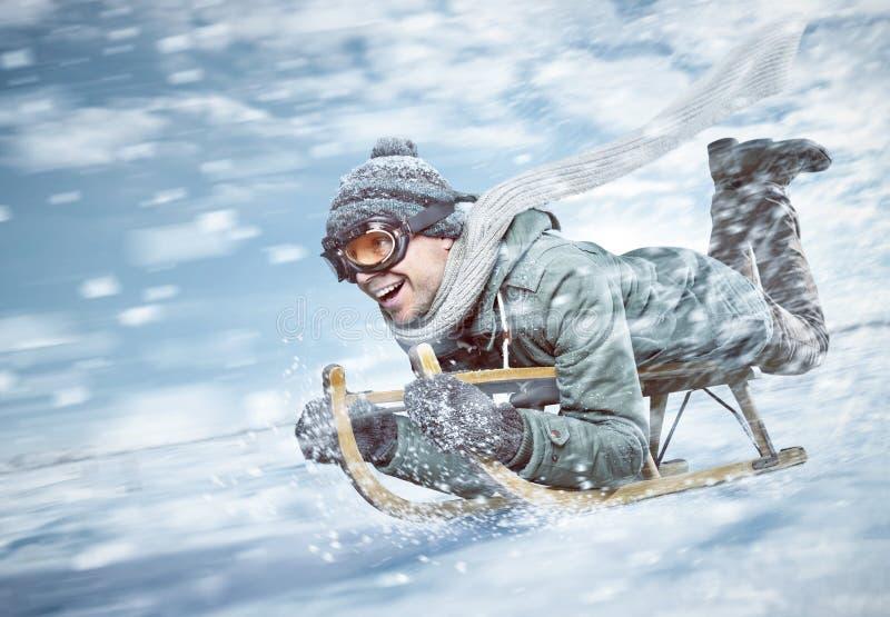Netter Mann, der hinunter eine schneebedeckte Steigung in der vollen Geschwindigkeit rodelt lizenzfreie stockfotos