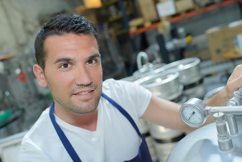 Netter Mann in der weißen Uniform unter Verwendung der abfüllenden Ausrüstung auf Brauerei stockbilder
